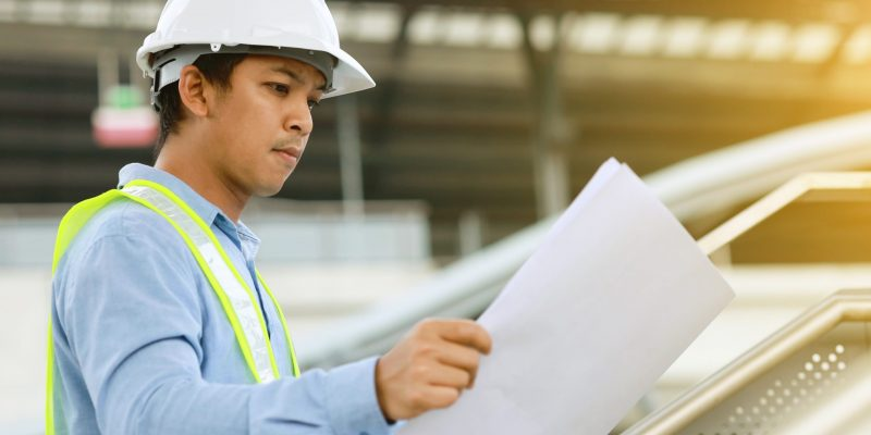 Engineer,Look,At,Blueprint,Draft,Paper,At,Construction,Site